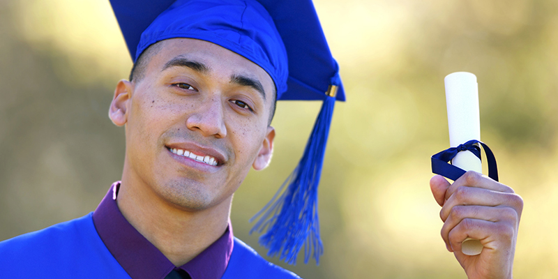 Hispanic Male holding his diploma while wearing cap and gown
